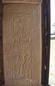 Detalle de la jamba de la puerta de acceso, en cuya parte inferior se puede apreciar las figuras de un saltimbanqui y un domador de leones.